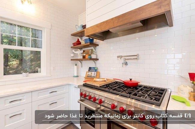 قسمتی از یک آشپزخانه با اجاق گاز با دسته های قرمز و یک قفسه کتاب چوبی کنار گاز