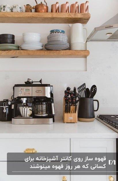 گوشه ای از کانتر یک آشپزخانه با قفسه های چوبی و قهوه ساز مشکی و نقره ای