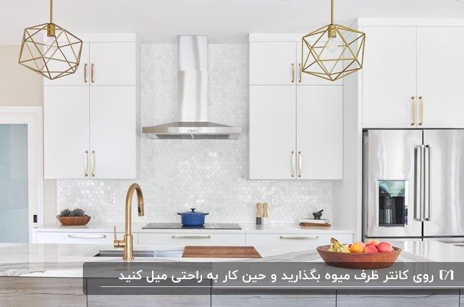 آشپزخانه ای سفید با شیرآلات طلایی و کاسه میوه ای چوبی روی کانتر