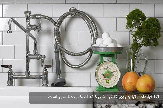 شیرآلات نقره ای یک آشپزخانه به همراه ترازوی آشپزخانه سبز و سبزیجات