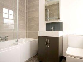 حمام کم عرض با وان سفید و روشویی چوبی