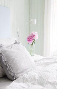 تصویر اتاق خواب رمانتیکی با پرده های سفید و گل های طبیعی