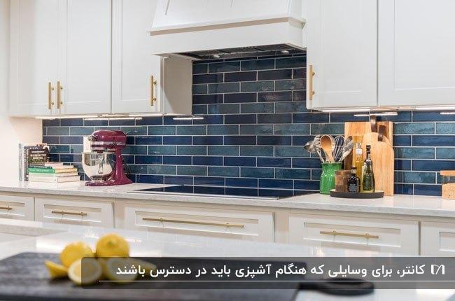 آشپزخانه ای با کاشی های افقی سرمه ای براق و کابینت های سفید تمام لوازم مورد نیاز آشپزی کنار گاز