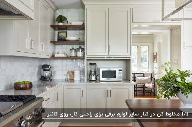 آشپزخانه ای با کابینت های کرم رنگ به همراه ماکرویو و مخلوط کن کنار یکدیگر