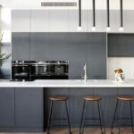 آشپزخانه ای به رنگ طوسی با لوستر آویزان و صندلی کانتر