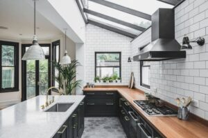 تصویر آشپزخانه ای با کابینت مشکی ، کاشی های سفید دیوار و طوسی کف