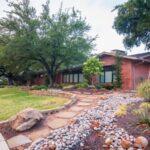 فضای باز و باغچه ورودی خانه ای با آجر نمای قرمز