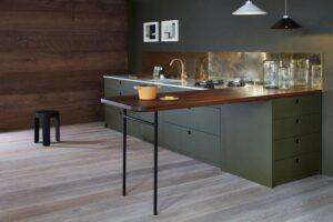 تصویر آشپزخانه ای شیک با کابینت های سبز تیره و طراحی برنج برای دیوار آن