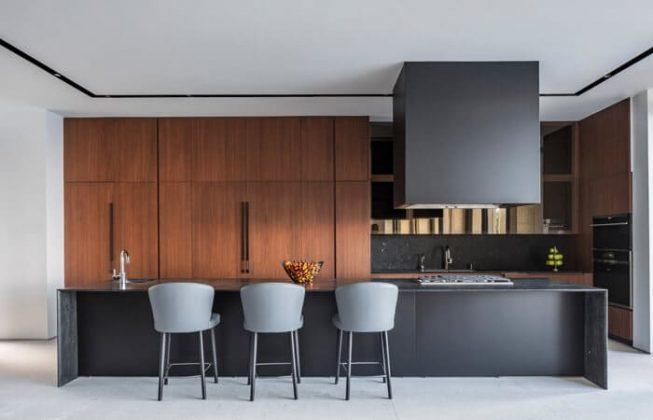 تصویر یک آشپزخانه به سبک مدرن با تم رنگی تیره به همراه چوب
