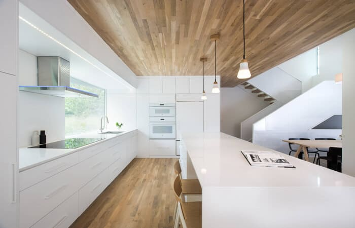 تصویری از یک آشپزخانه مدرن سفید با سقف و کف چوبی