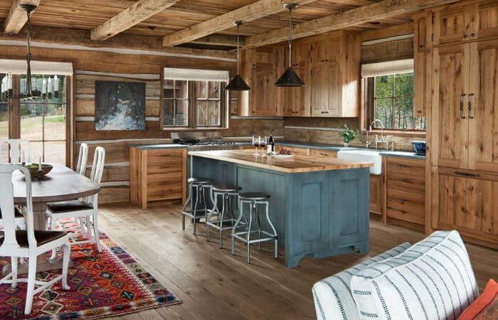یک آشپزخانه روستیک از لوسترهای آویز مشکی رنگ تزیین شده است