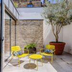استفاده از میز وصندلی زرد رنگ فلزی در حیاط خلوت