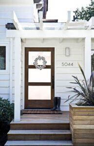 تصویری از درب ورودی چوبی یک خانه با نمای سفید