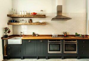 تصویر آشپزخانه ساده ای با کابینت های مشکی و رویه ای از جنس چوب