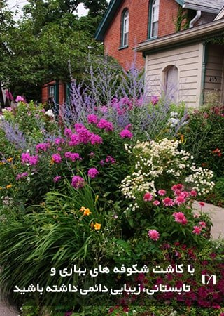 باغچه خانه ای که از دو طرف گل کاری شده است و پیاده رو را زیبا کرده