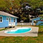 تصویر خانه ای با نمای آبی رنگ و استخر منحنی کوچک