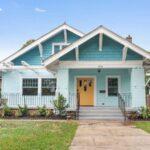 تصویری از نمای خارجی یک خانه با استفاده از آبی های تیره و روشن و درب زرد