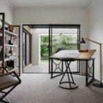 تصویری از یک اتاق کار با میز طراحی چوبی و درب شیشه ای بزرگ