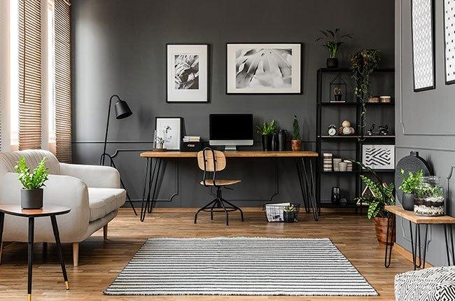 میز کار با کامپیوتر و دیوارهای طوسی و مبل سفید