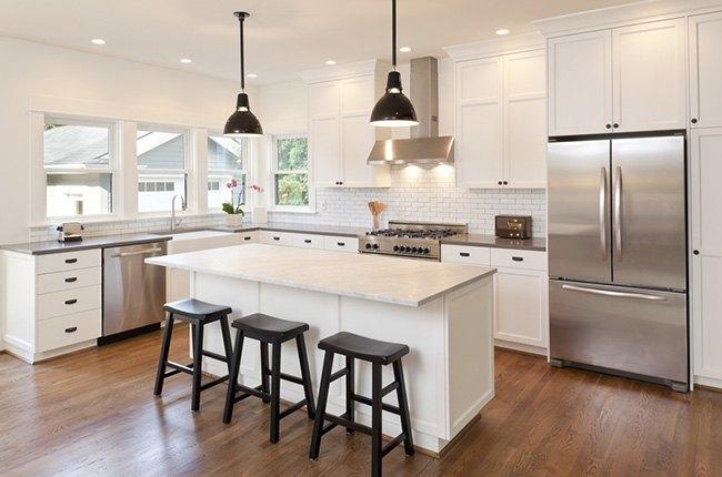 آشپزخانه با جزیره بزرگ و سفید با سه صندلی کانتر