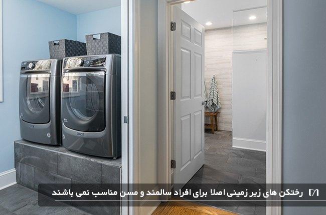 رختکن با دو عدد ماشین لباس شویی طوسی و بزرگ در اتاق