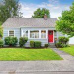 تصویر خانه ای با نمای طوسی و درب قرمز رنگ