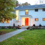 تصویری از یک خانه با نمای سفید و درب ورودی قرمز رنگ