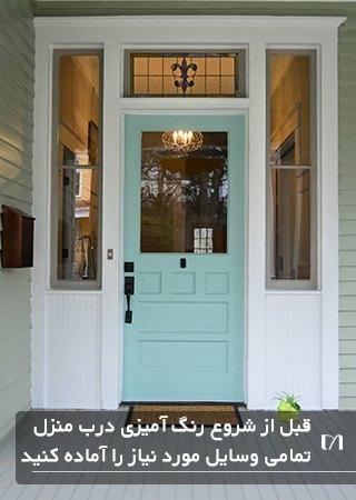 تصویری از یک ورودی زیبا با درب به رنگ سبز پاستلی و پنجره های باریک و بلند اطراف درب