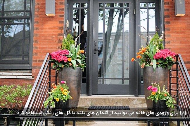 ورودی خانه ای زیبا با گلدان های بلند و گل های بهاری رنگی