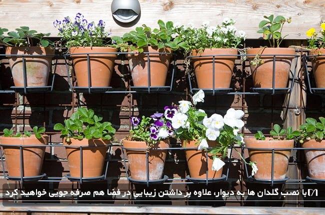 باغچه بهاری دیواری چیدمان شده با گل های بهاری و گلدان های سفالی