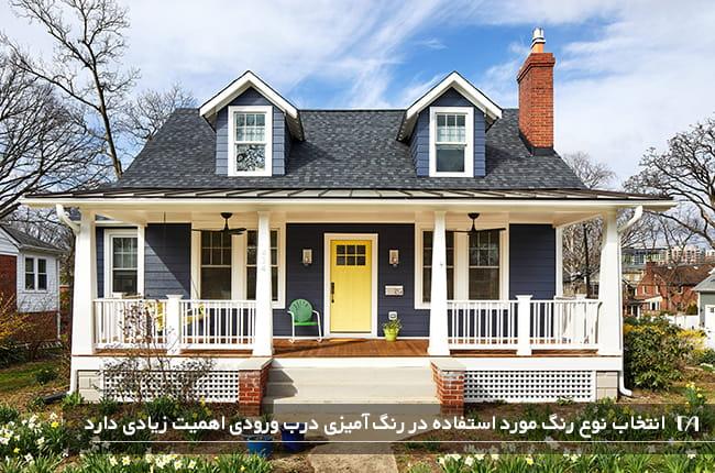 تصویری از محوطه ورودی یک خانه با نمای سرمه ای و درب زرد رنگ