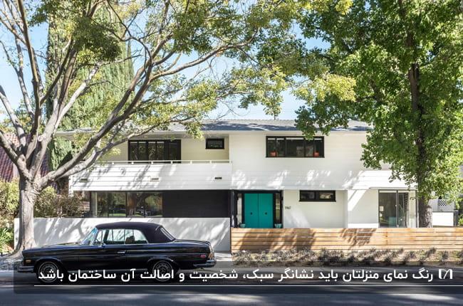 خانه ای ویلایی با نمای سفید و پنجرهای مشکی و درب ورودی آبی فیروزه ای با یک ماشین مشکی جلوی درب