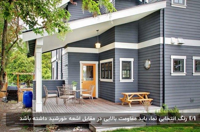 ویلایی با نمای خاکستری و سفید، درب چوبی و ایوان با کفپوش ترموود