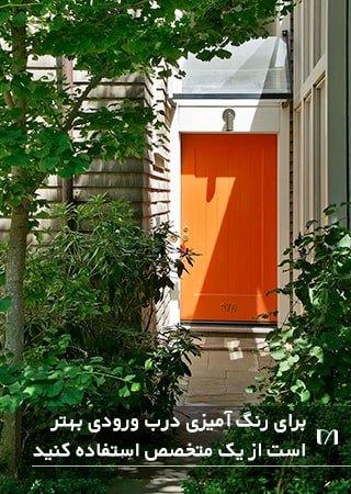 تصویر طراحی یک درب زیبای نارنجی که توسط یک متخصص رنگ آمیزی شده است