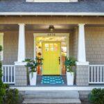 تصویر یک محوطه ورودی با دیوارهای طوسی ، ستون های سفید و درب زرد