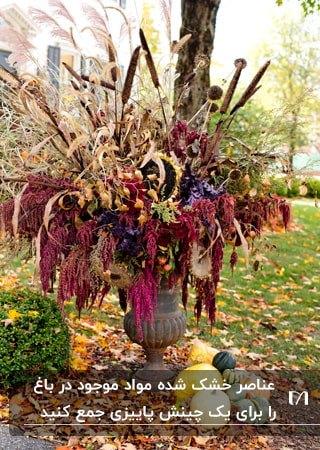 تصویر گلدانی پاییزی با عناصر خشک شده و کدوهایی اطراف گلدان برای زیبایی