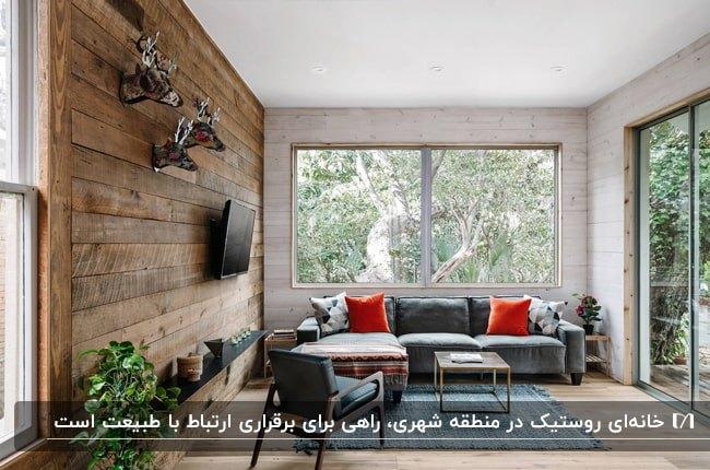 نشیمنی روستیک با دیوارپوش چوبی، مبل خاکستری، کوسن قرمز و گوزن های دیواری دکوری