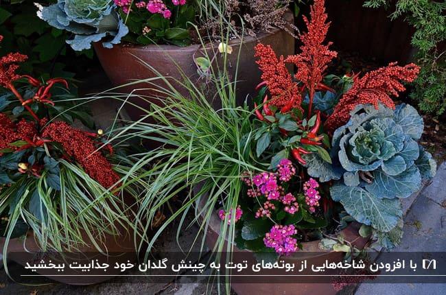 گلدانی پاییزی که با شاخه های بوته توت و گیاهان سبز تزیین شده است