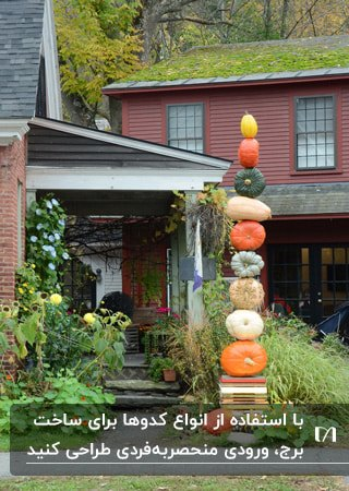 ورودی خانه ای با دکور پاییزی برجی از انواع مختلف کدوها روی یکدیگر