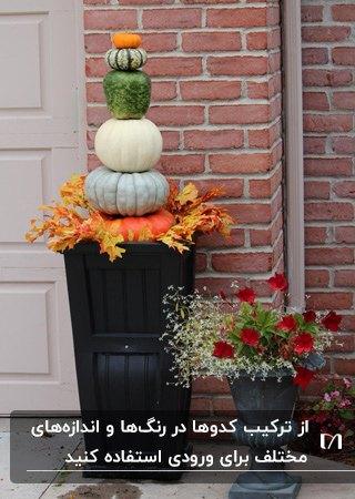 ورودی خانه ای با تزئین پاییزی گلدانی مشکی با شش نوع کدوی مختلف روی هم