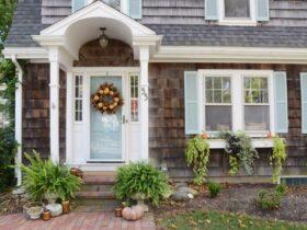 تصویر نمای خارجی ویلایی با تخته های چوبی، سقف شیروانی و دکور پاییزی کدو