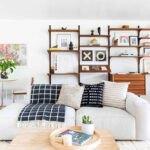اتاق نشیمن با مبل های سفید راحتی و قفسه چوبی