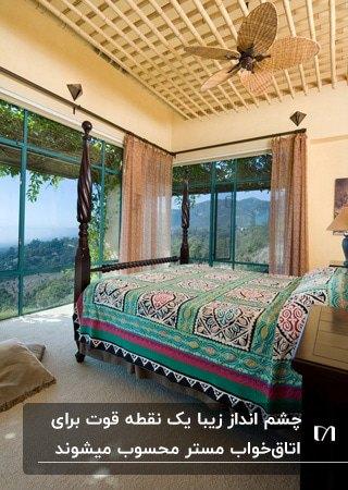 اتاق خوابی مستر با تخت خواب وسط اتاق، دیوارهای شیشه ای با چشم انداز کوهستان