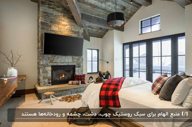 اتاق خوابی به سبک روستیک با شومینه و تلویزیون روی دیوار سنگی مقابل تخت