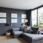 اتاق با دیوار و مبل های تیره و پنجره بزرگ و سقف کوتاه