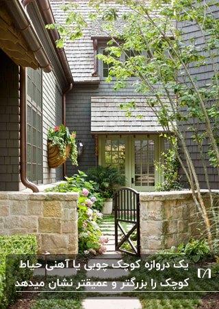 دروازه کوچک فلزی مشکی رنگی کنار دیوار کوتاه سنگی یک حیاط کوچک