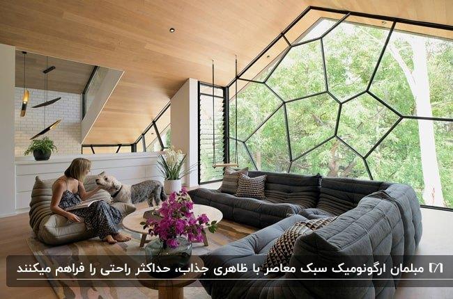 خانه ای به سبک معاصر با مبلمان راحتی خاکستری، دیوار چندضلعی شیشه ای با حفاظ فلزی