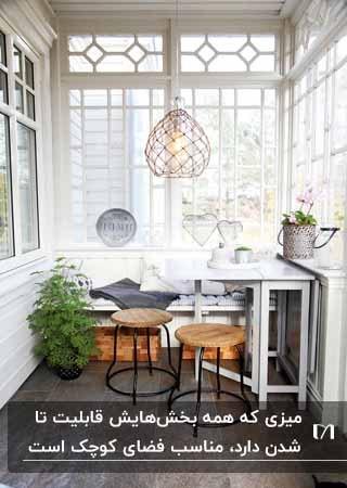 بالکن کوچکی با میز تاشو سفید کنار دیوار و دو چهارپایه فلزی و چوبی زیر پنجره