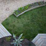 تصویر حیاط یک ویلا با طراحی باغچه های نیم دایره