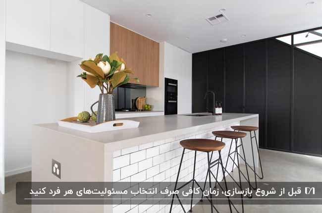 آشپزخانه ای با کابینت ها ترکیبی سفید و چوبی، جزیره سفید آجری و چهارپایه های چوبی و فلزی